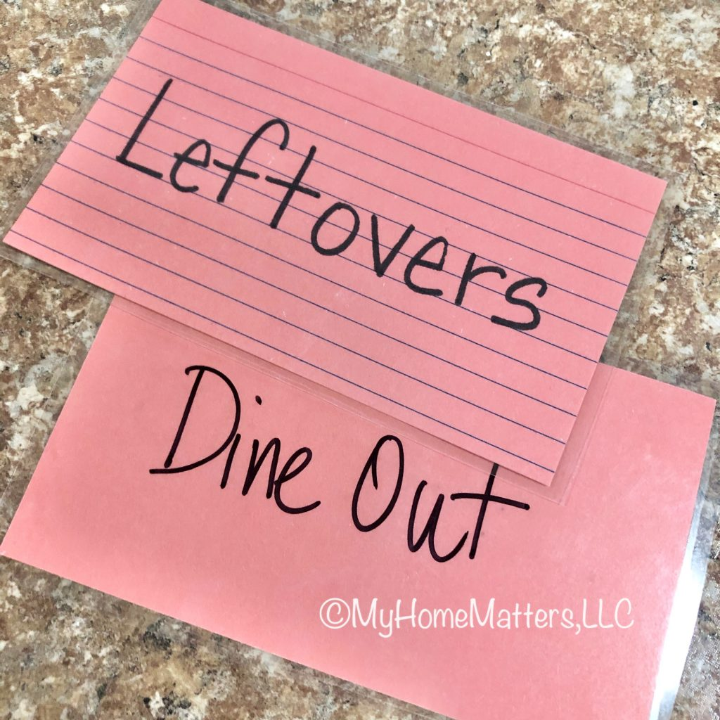"""salmon colored index cards labeled """"leftovers"""" and """"dine out"""""""