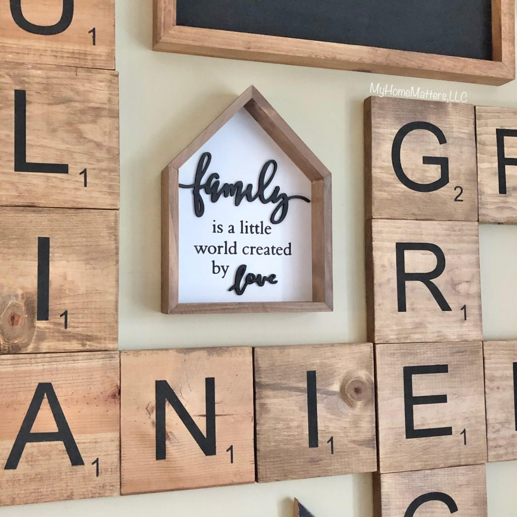 a house shaped sign hanging on a wall