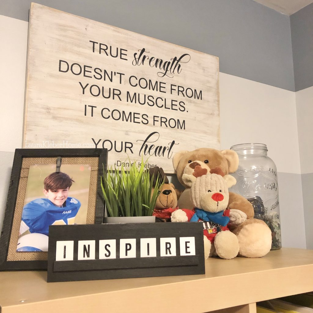 a shelf with stuffed animals and photo frame and motivational sign