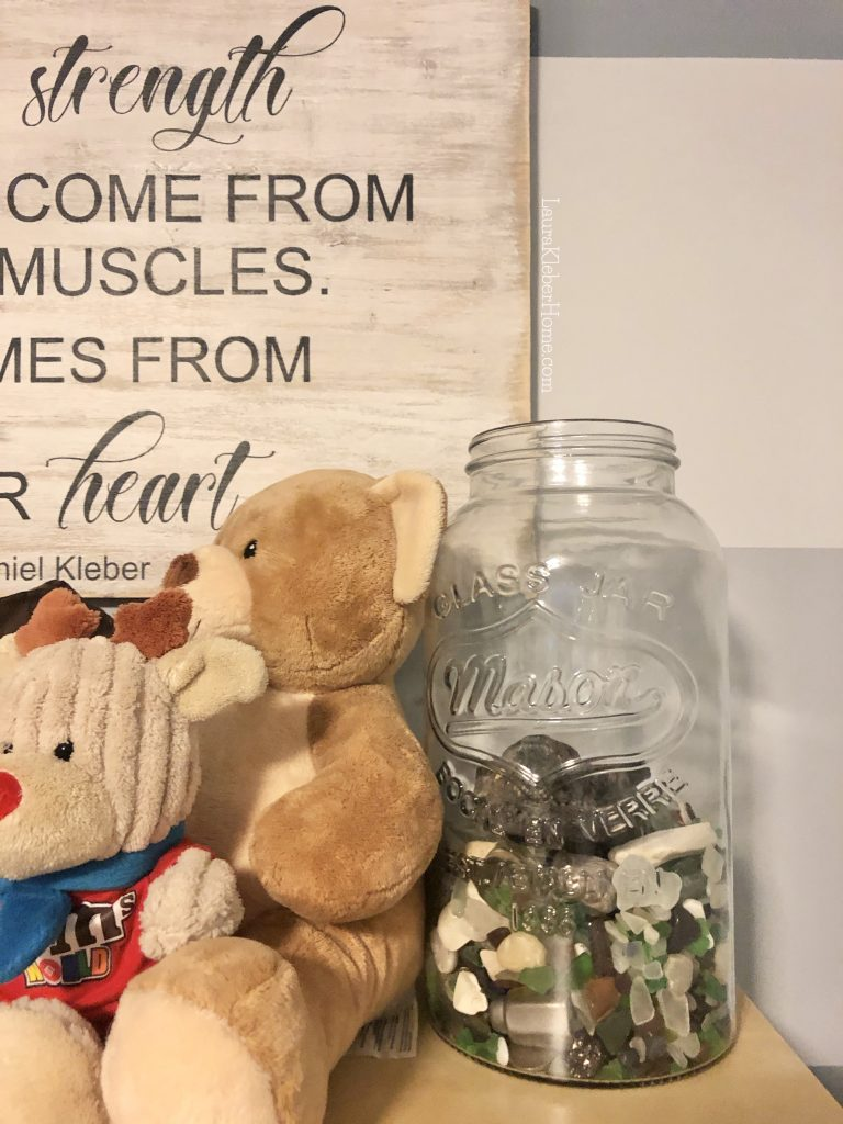 a shelf with a jar of glass and stuffed animals