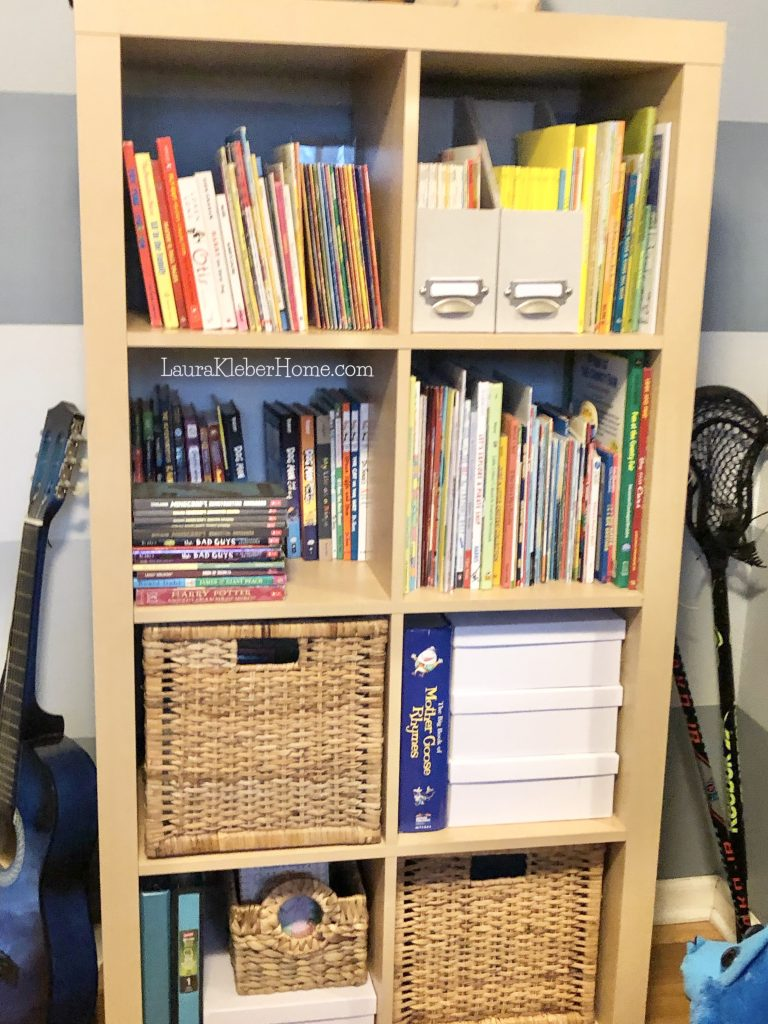 cube shelf unit with books and bins on it