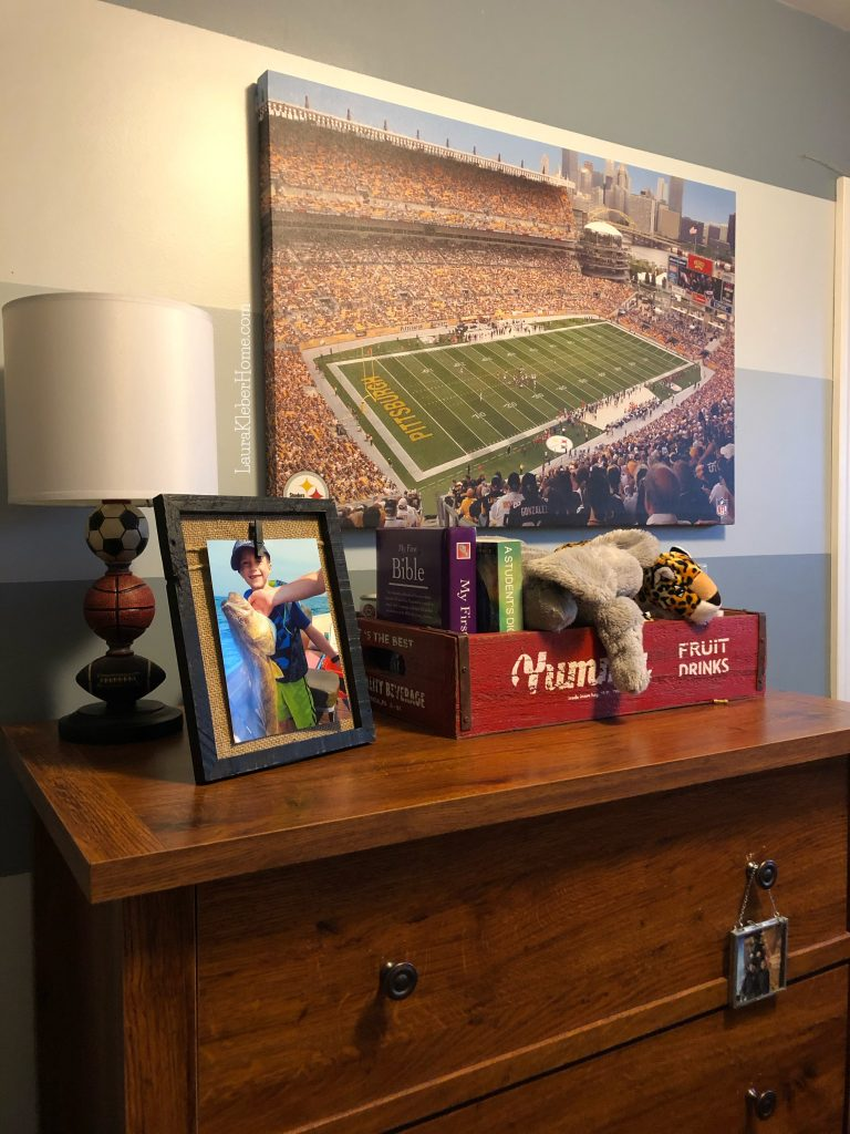 dresser top decorated with a crate of stuffed animals and sports photos