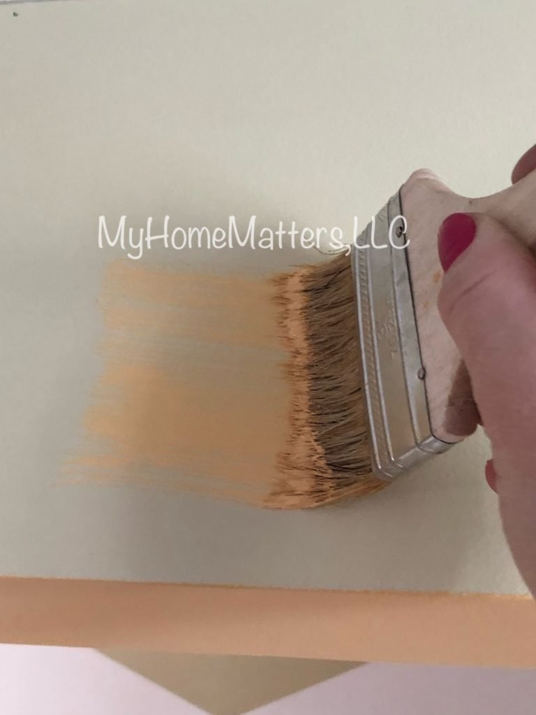 starting to apply yellow paint to a wall using a brush