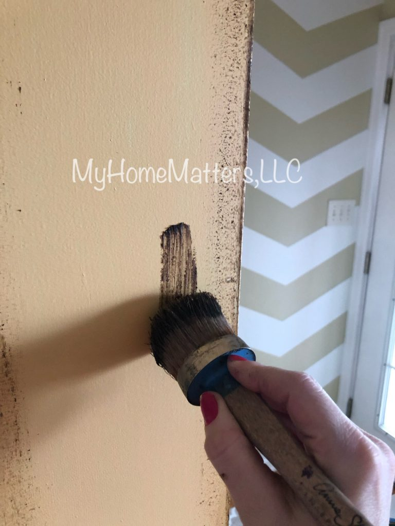 starting to apply wax to a wall with a brush