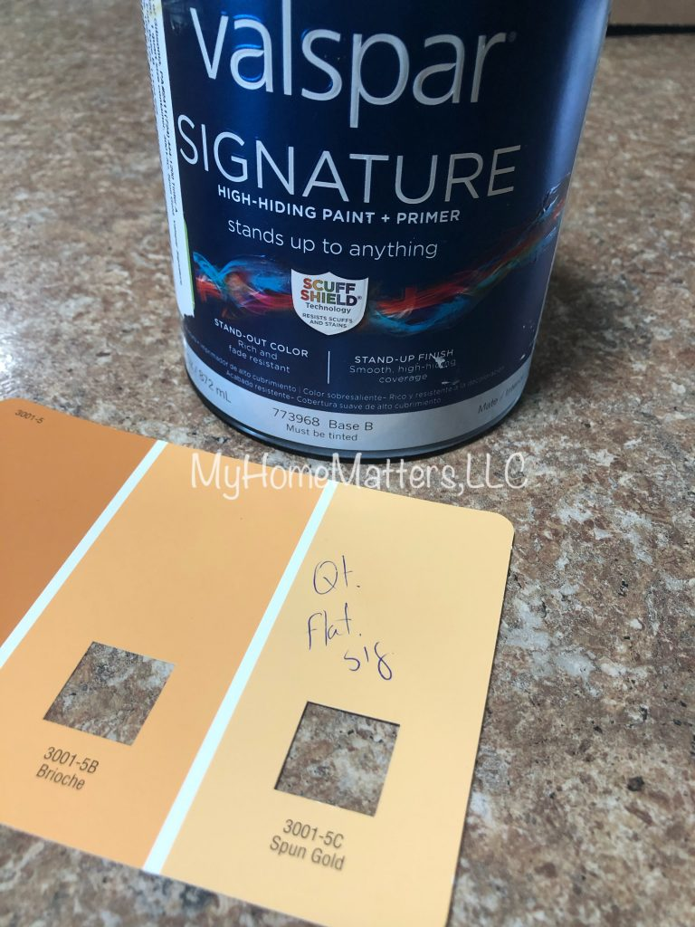 paint can and paint swatch sample in orangeish yellow
