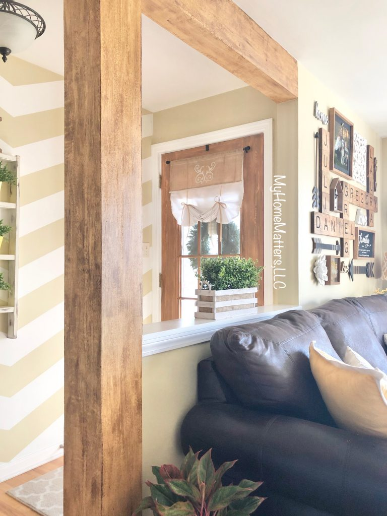 a wooden door and wooden beams in a living room and entryway