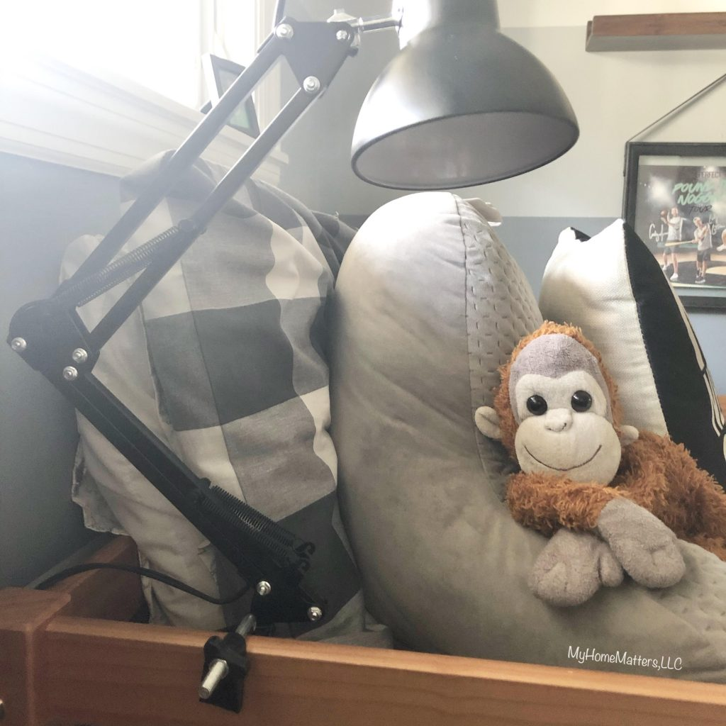 a swivel lamp and stuffed monkey on a boy's bed