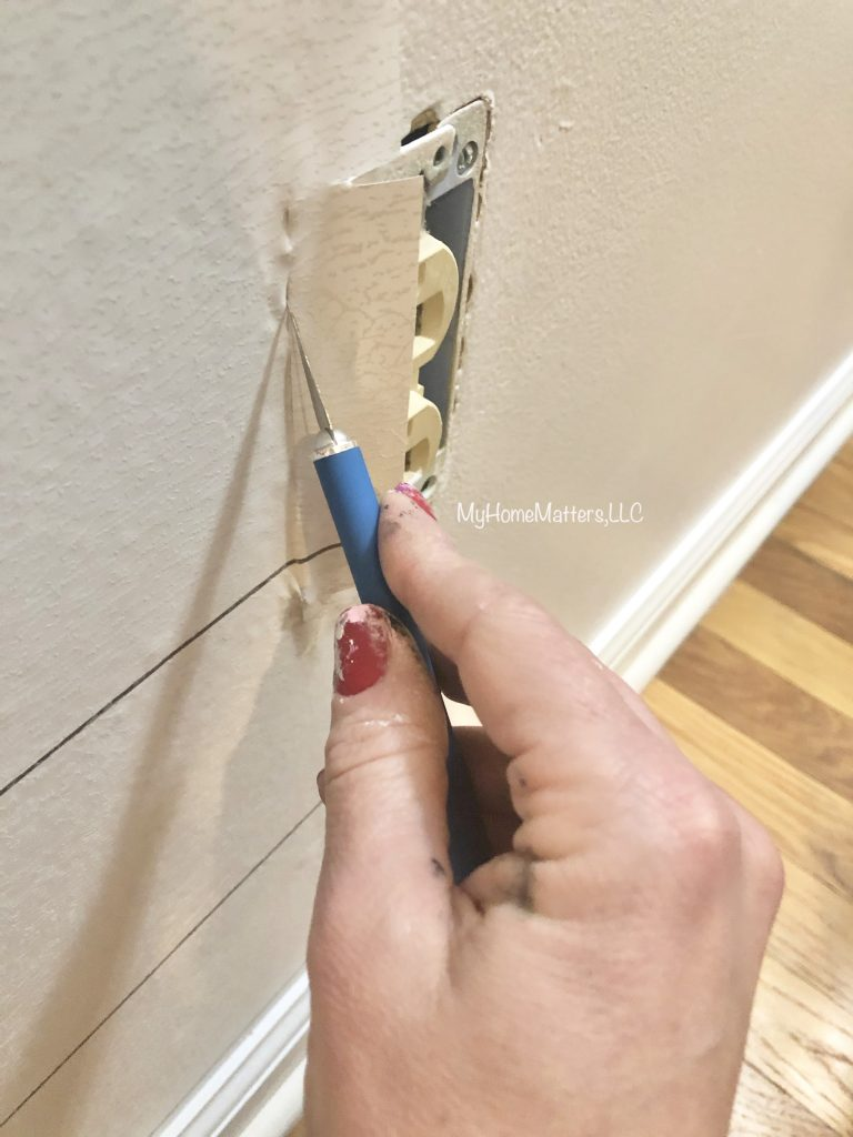 person cutting out the outlet while installing wallpaper