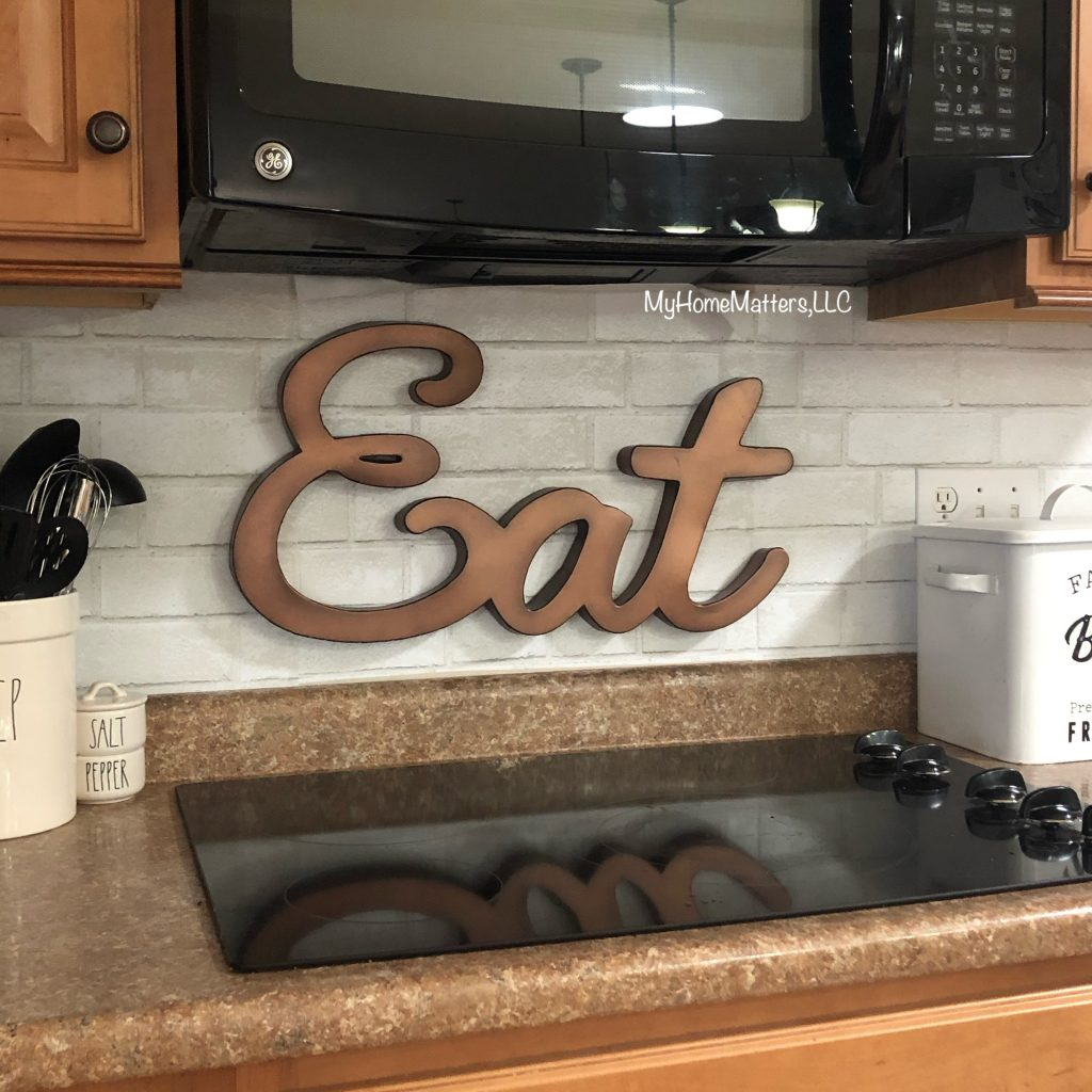 kitchen stove area with metal wall art hanging above stove