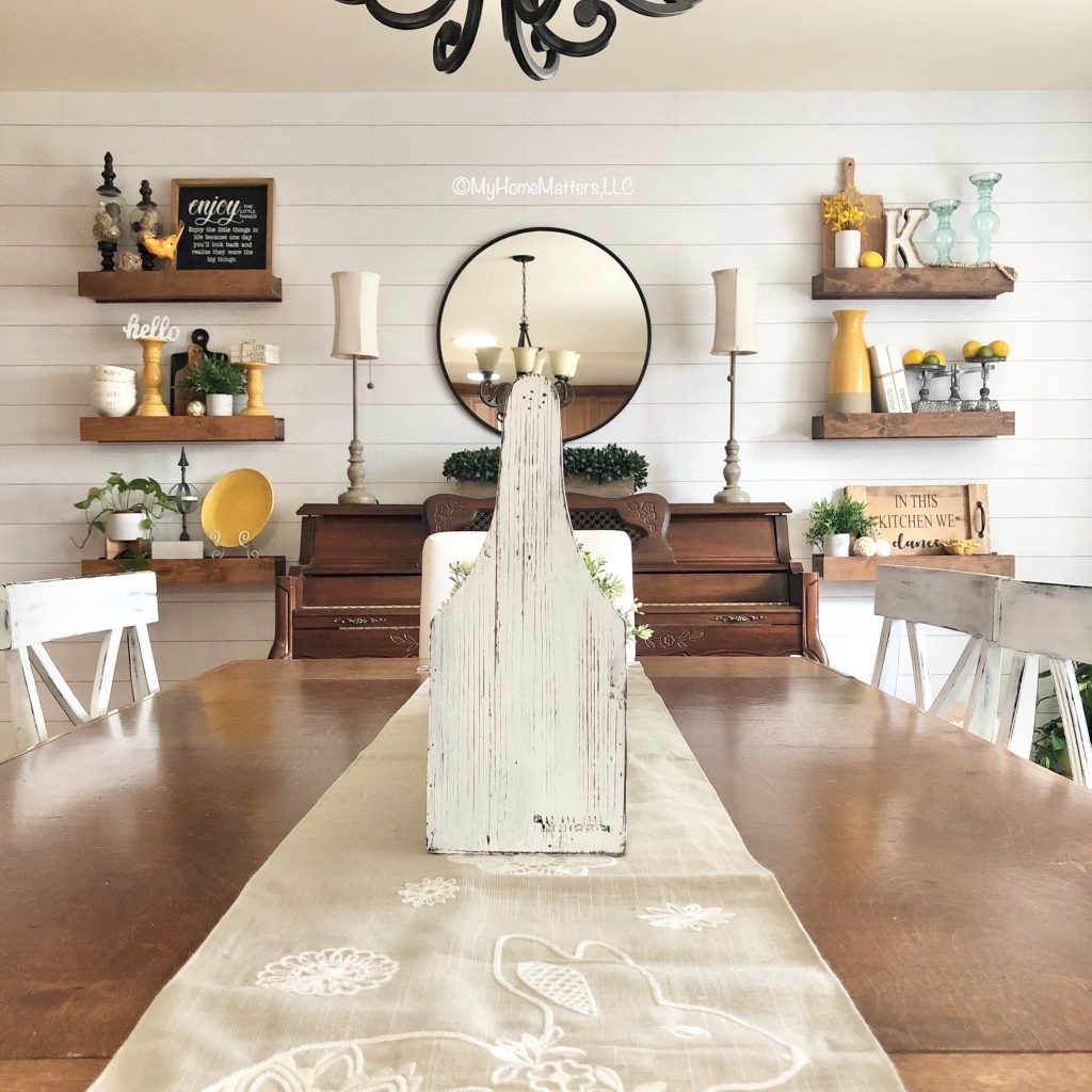 dining room with table and shiplap wall, piano and chunky floating shelves