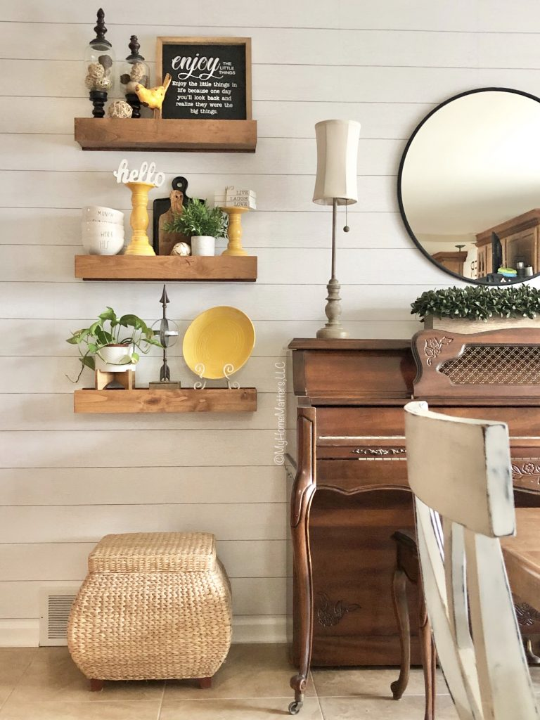 shiplap wall with chunky floating shelves and a piano