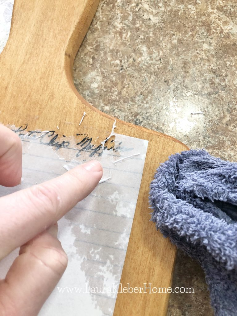 person using finger to peel away paper in an image transfer