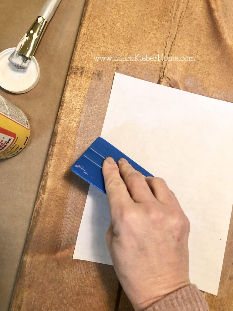 person using squeegee to apply paper to a piece of mod podged wood