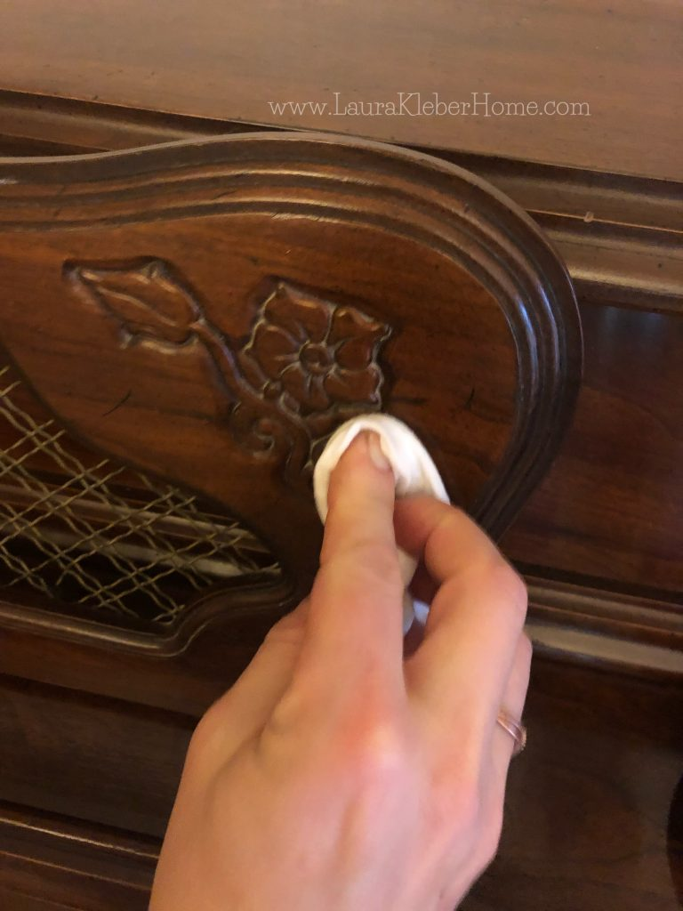 someone's hand cleaning a piano