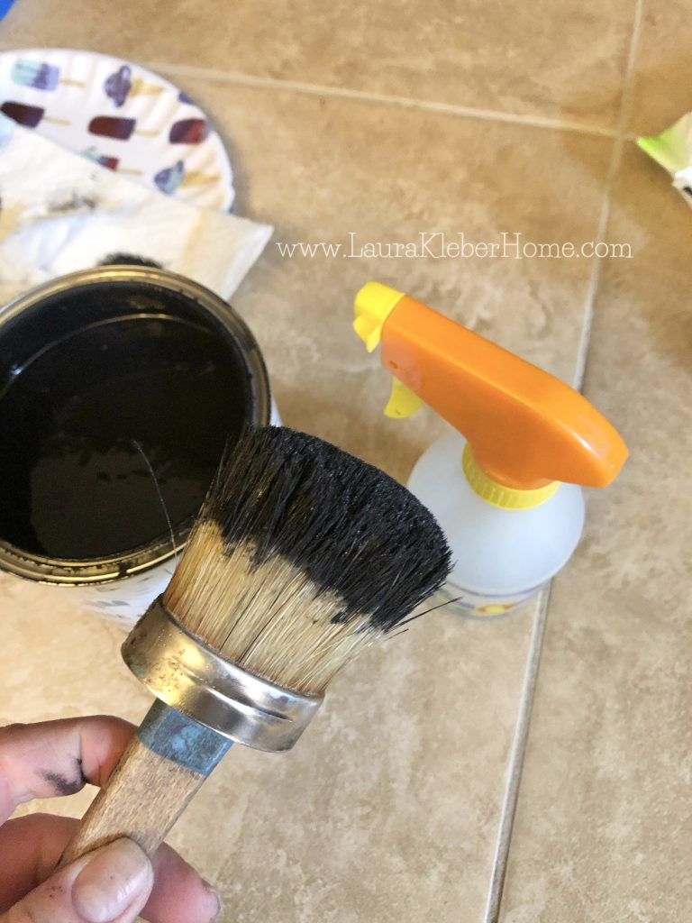 can of black paint, paint brush and spray bottle