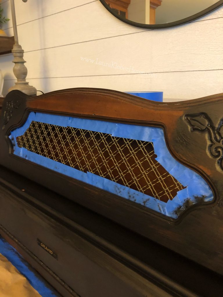 blue painter's tape used to mask off a piano being painted