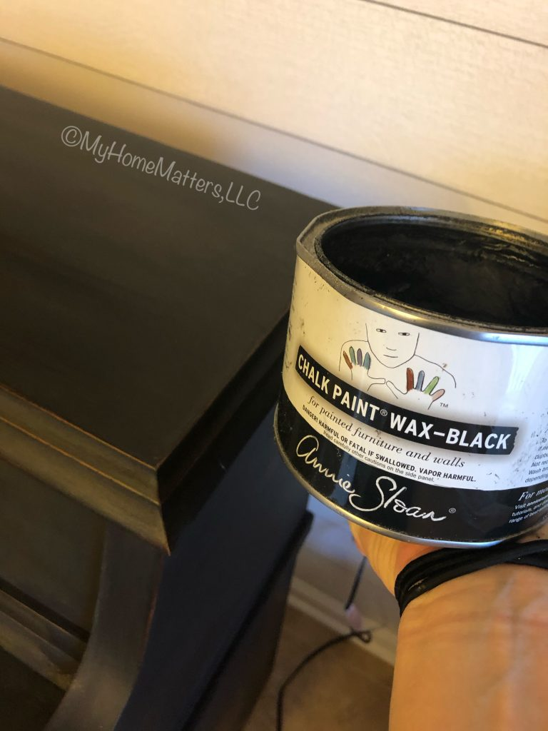 can of Annie Sloan black wax beside a black painted piano