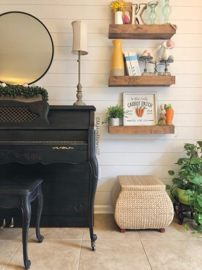 close up view of a black painted piano on a shiplap wall and floating wood shelves