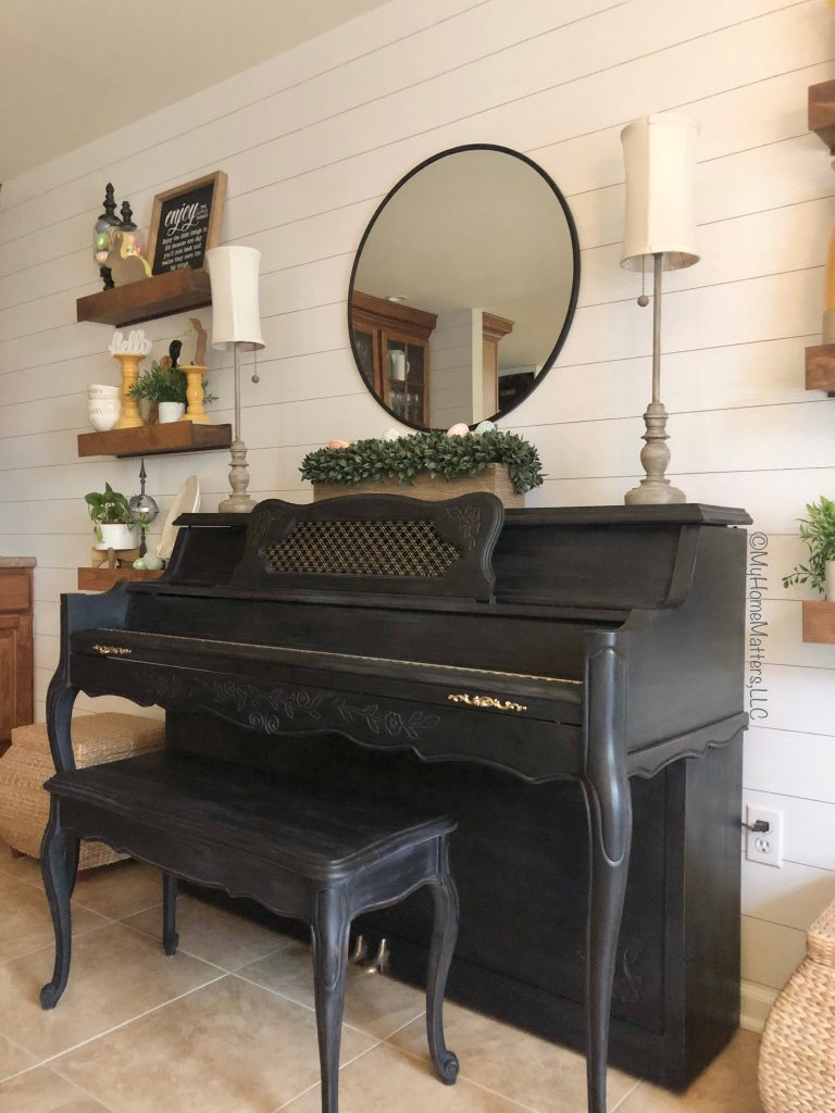 black painted piano on a shiplap wall