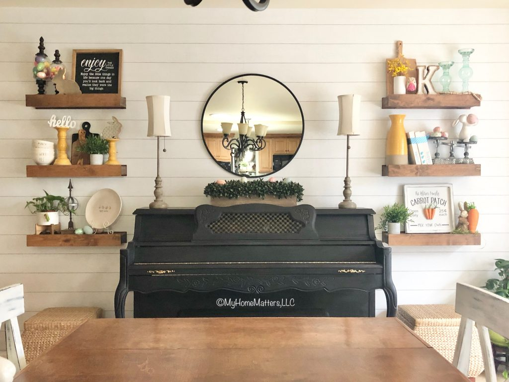 black painted piano and wood floating shelves on a shiplap wall in a dining room