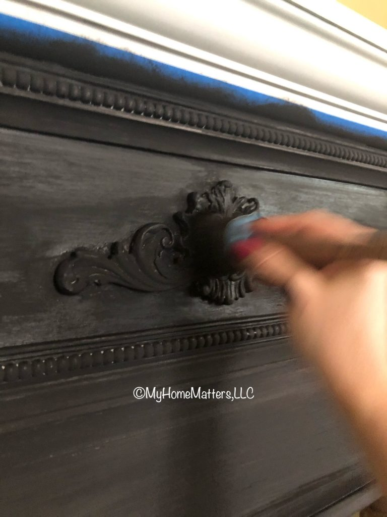 person's hand painting a fireplace black