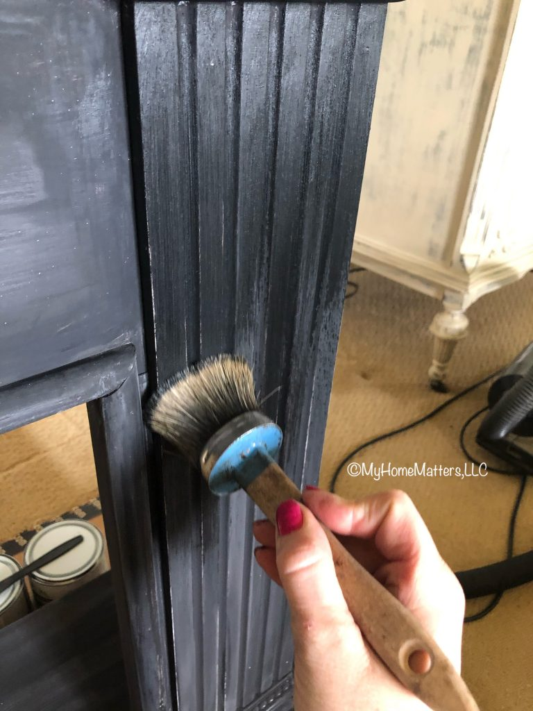 applying black wax to a faux fireplace painted in Athenian Black