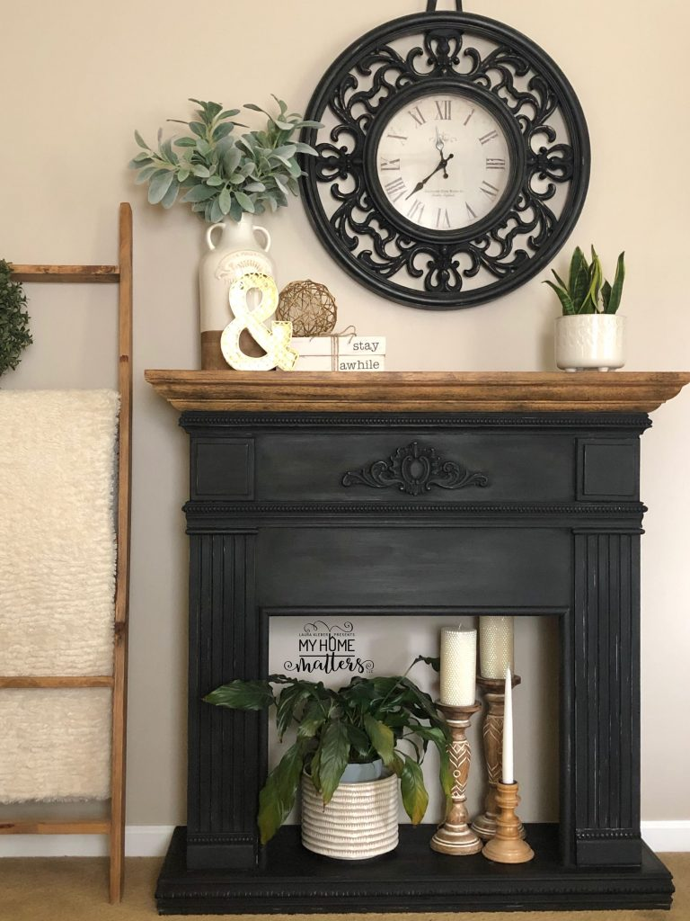black faux fireplace and black clock styled in a master bedroom