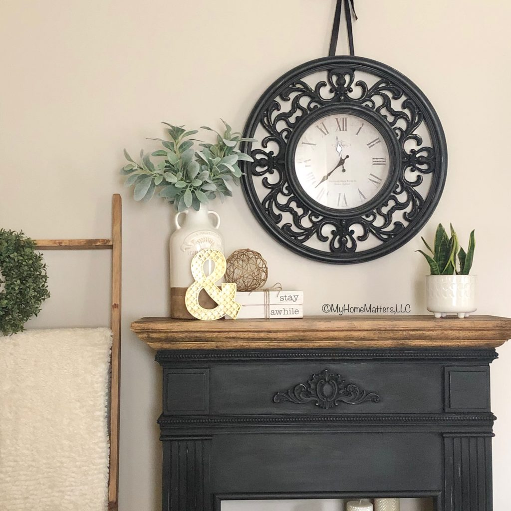 faux fireplace painted in black and a wood treatment styled with a black clock
