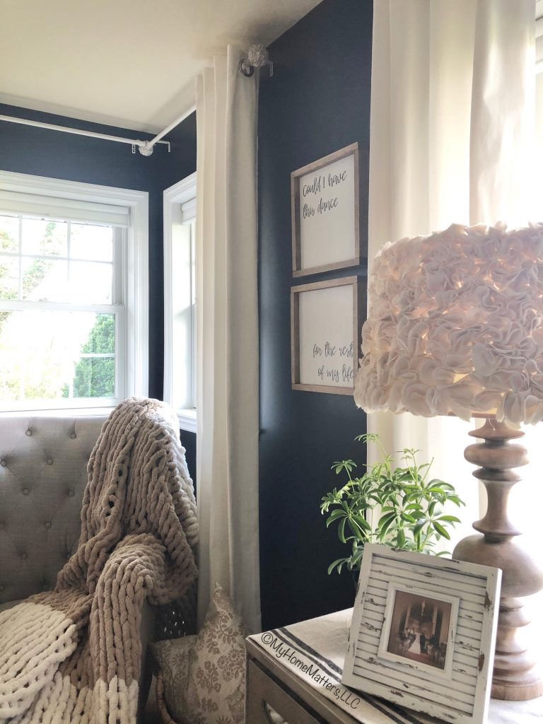 master bedroom view of side table, lamp, black wall, custom farmhouse signs and chunky blanket on a chair