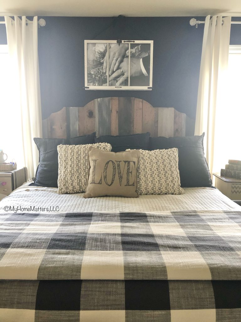 master bed with black wall, wooden headboard and buffalo checked bedding
