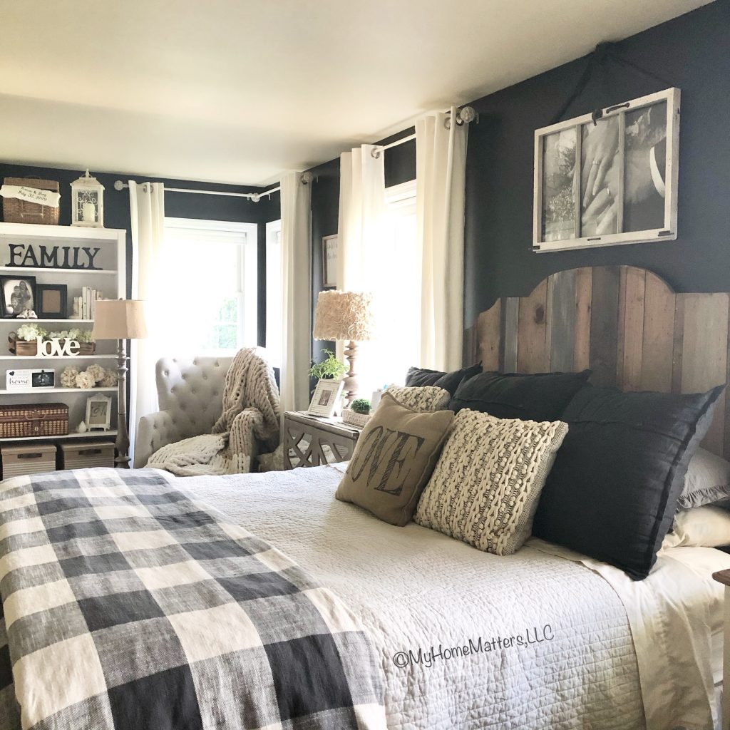 master bedroom view of buffalo check bedding, wooden headboard and black wall