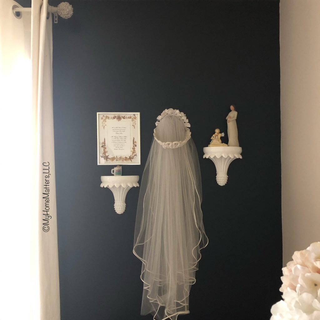wall arrangement with wedding veil and other trinkets on a black wall