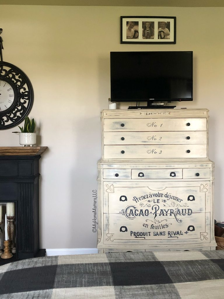 tall dresser painted cream and stenciled with French saying