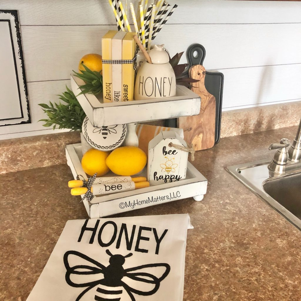 bee decorations on a tiered tray on a kitchen counter