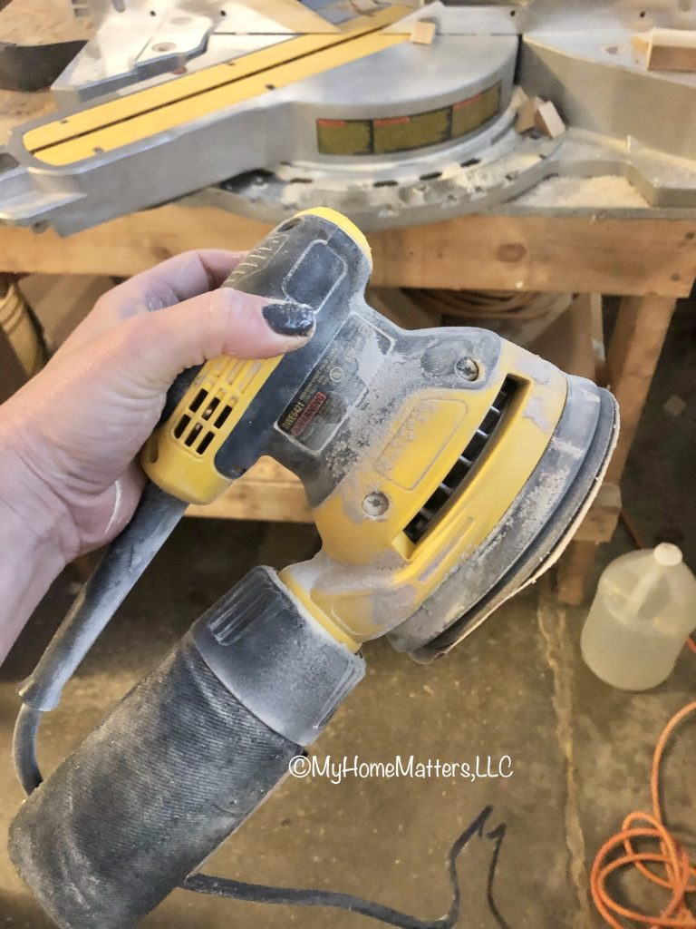 orbital sander being held in a dusty workshop