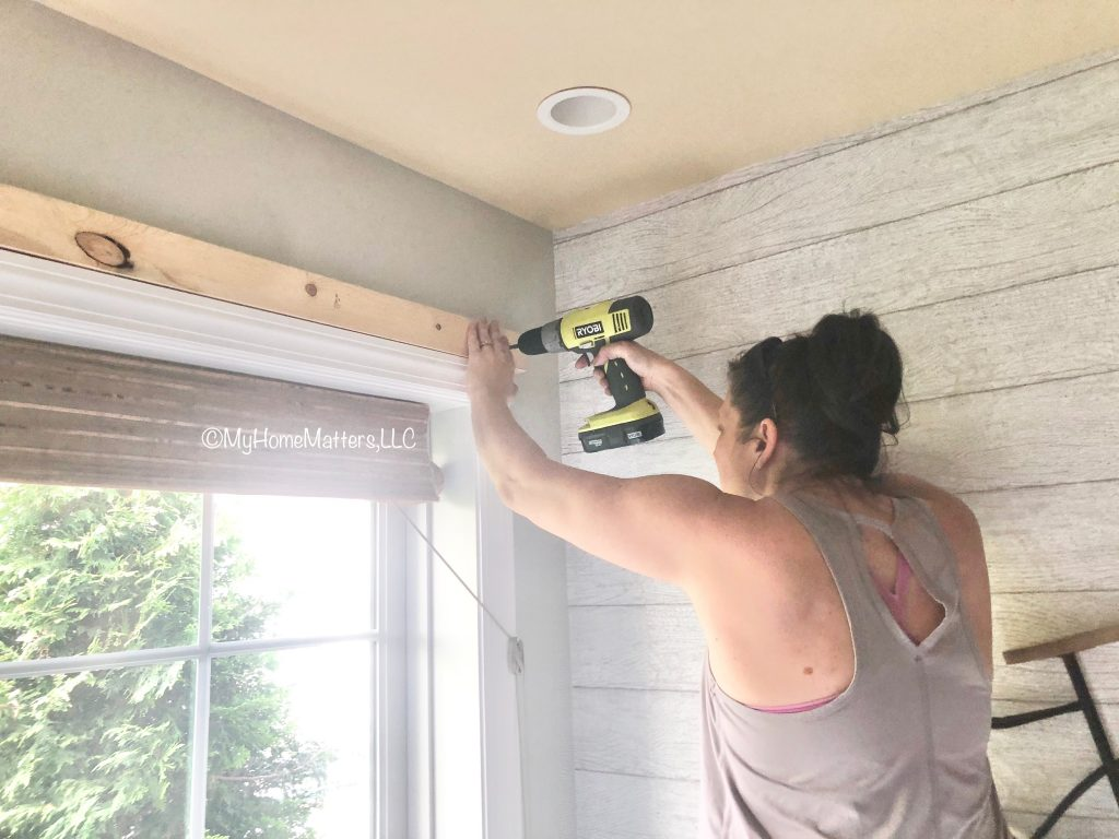 Laura attaching a piece of wood to wall with drill