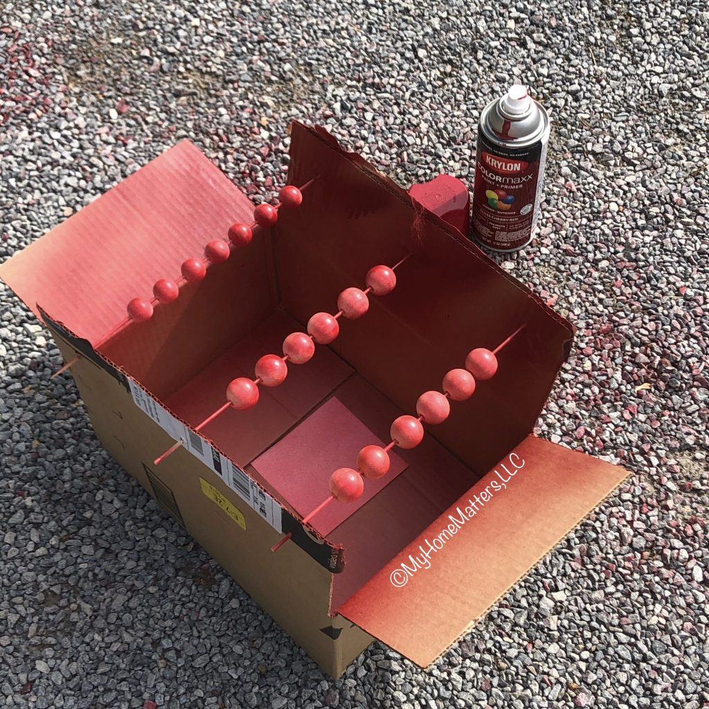 wooden beads being spray painted red