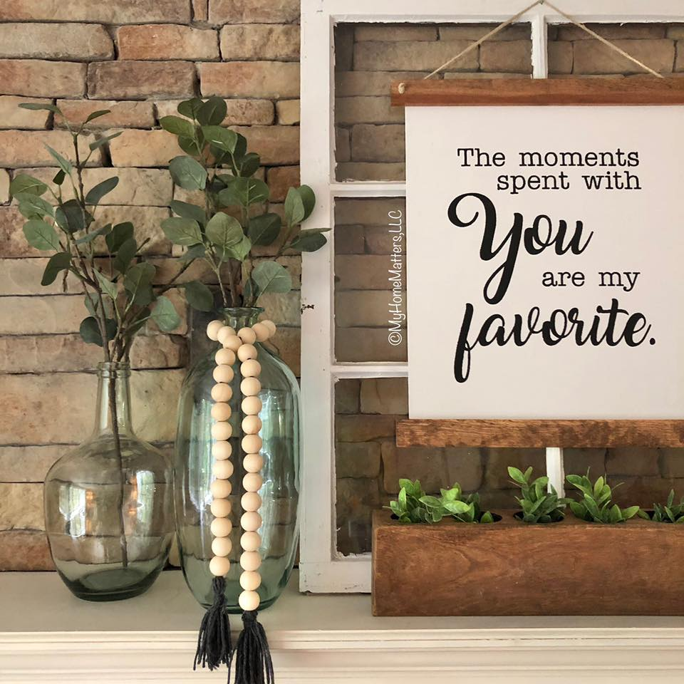 a mantel decorated with a vase, sign and wooden beads