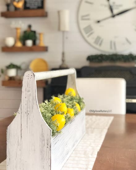 Toolbox filled with greens and lemons on dining room table