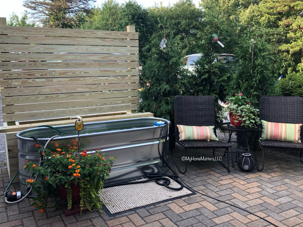 patio with outdoor fence bench and stock tank pool