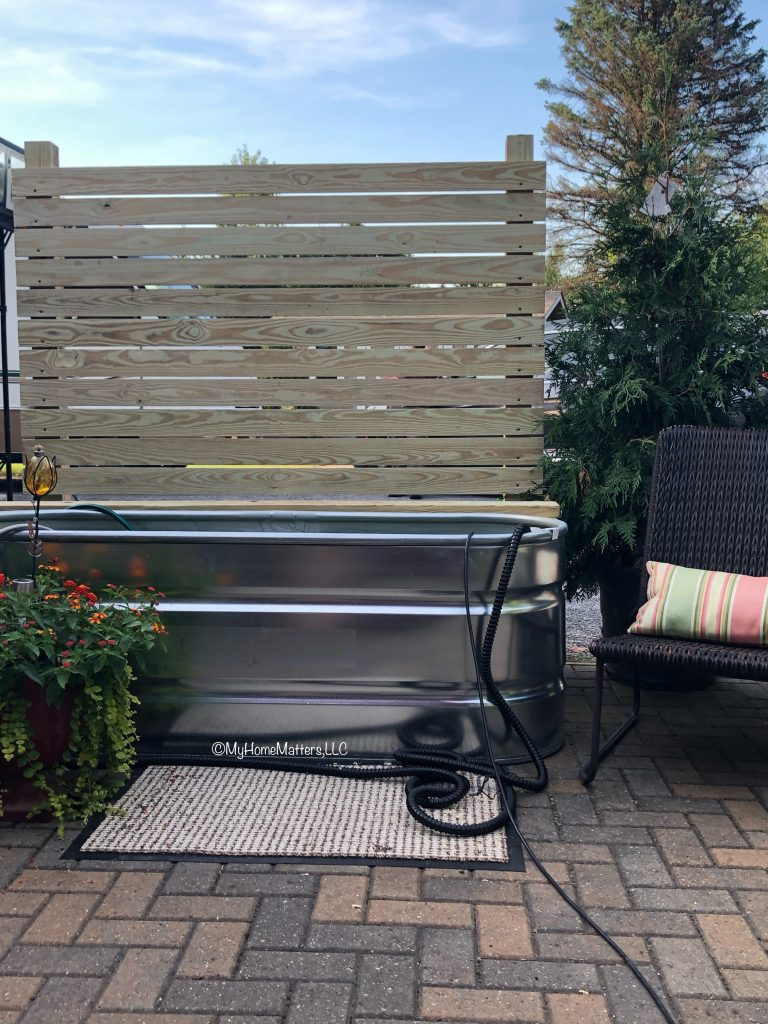 outdoor fence bench by stock tank pool