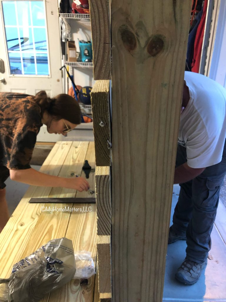 father and daughter assembling the seat of a bench