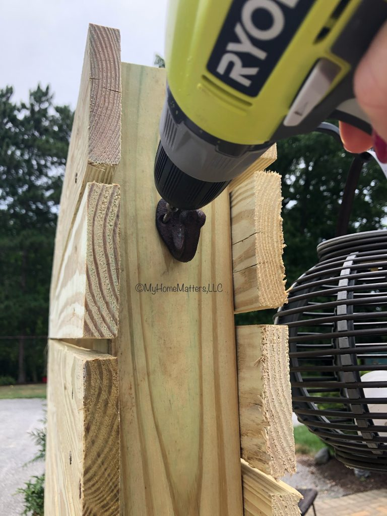 person drilling towel hooks into side of wooden post
