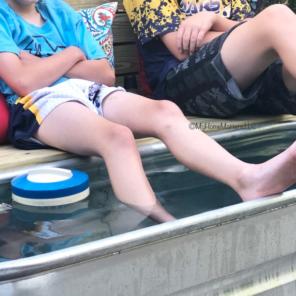 boys relaxing with feet in stock tank pool