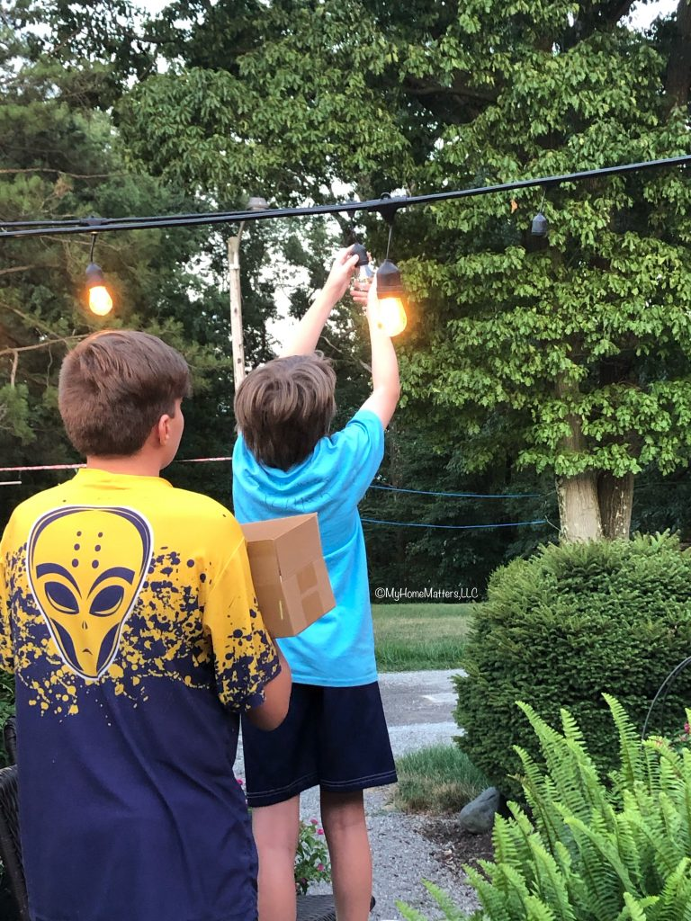 boys hanging string lights over a patio