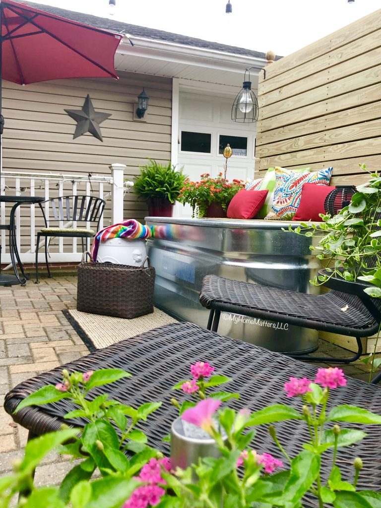 stock tank pool on a patio with fence and bench and decorative pillows