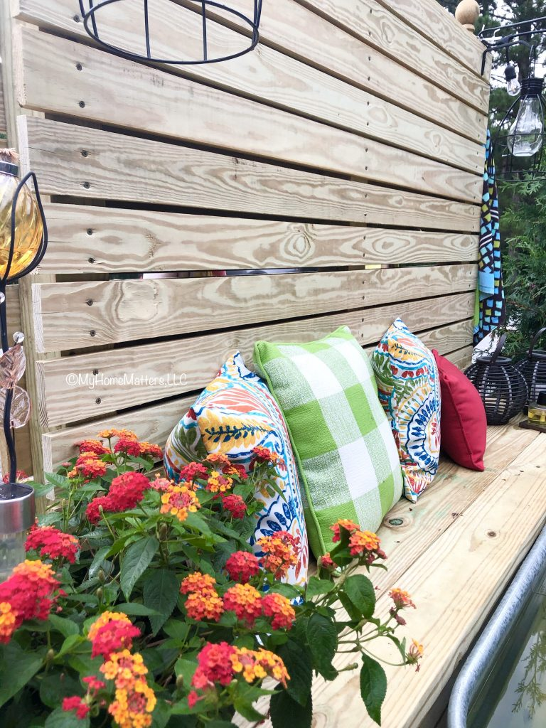 outdoor fence bench with pillows and hanging lanterns