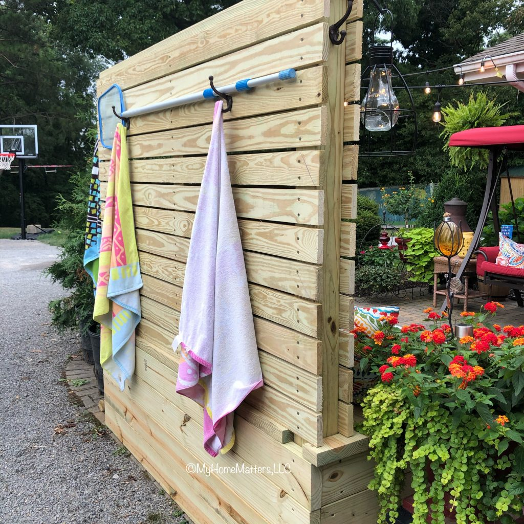 back of a fence with pool skimmer and towels hanging on hooks