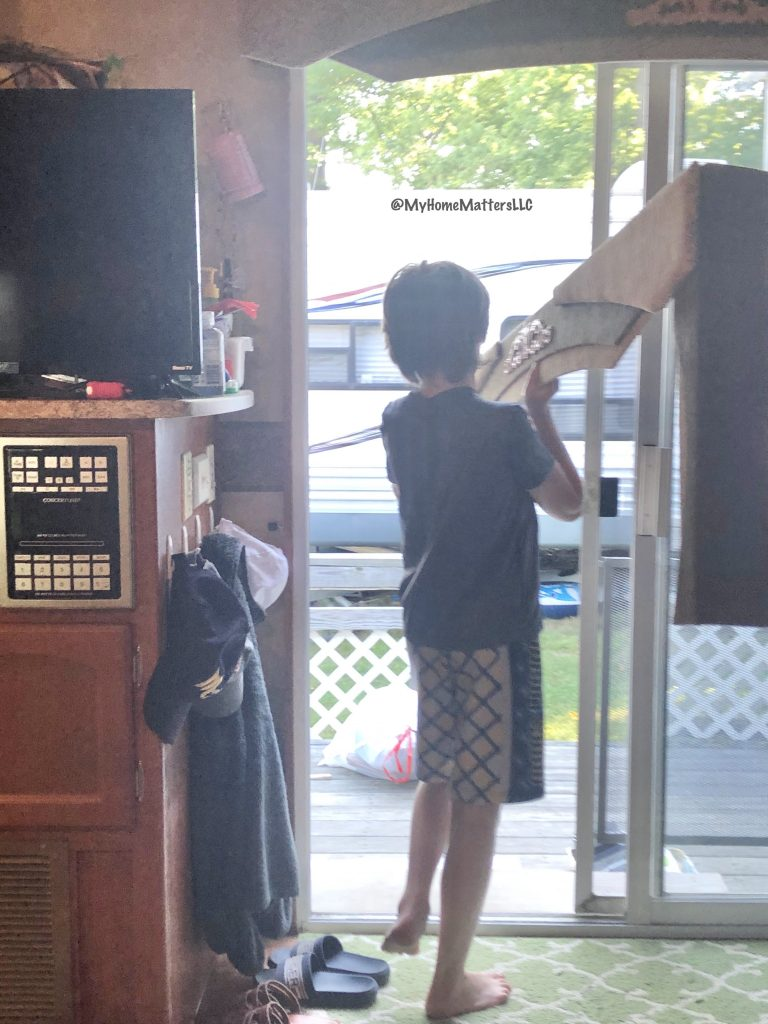 boy helping to remove bulky window coverings from a camper