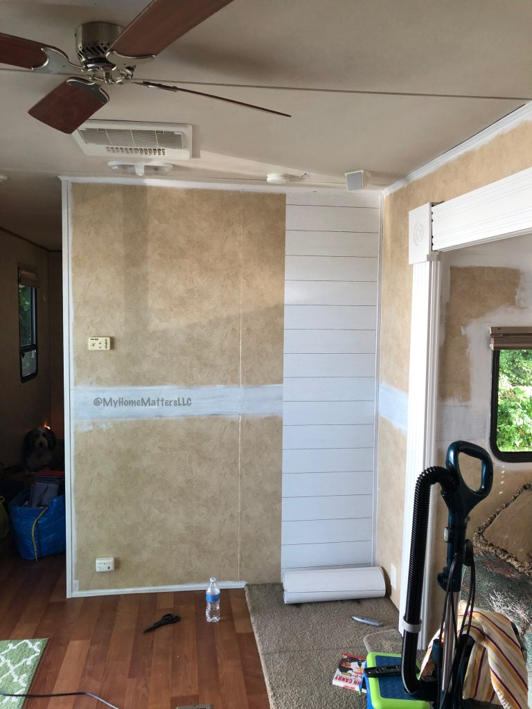 to show one roll of peel and stick shiplap wallpaper on the wall of a camper